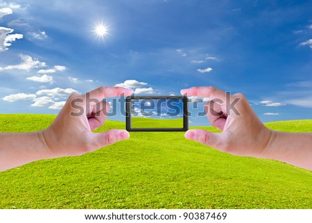 hand holding mobile phone and green grass meadow - stock photo