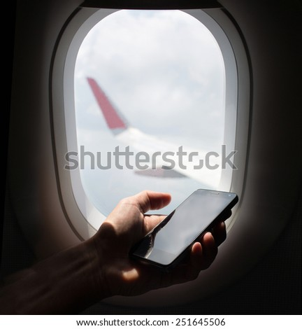 hand holding mobile phone with flight mode in the airplane  - stock photo