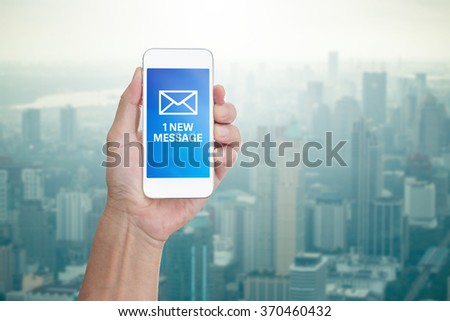 Hand holding mobile phone with 1 new message word on cityscape background - stock photo