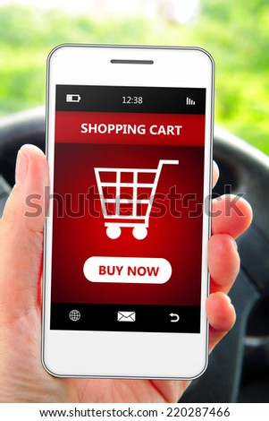 hand holding mobile phone with  shopping cart in the car - stock photo