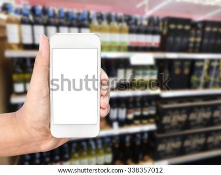Hand holding mobile smart phone on wine Liquor bottle on shelf, Blurred background - stock photo
