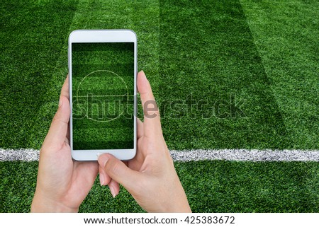 Hand holding mobile smart phone with football stadium, image of a football field as background. - stock photo