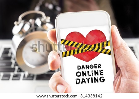 Hand holding mobile with caution tape on heart and Danger online dating  on screen with clock and laptop at background, Internet love concept. - stock photo
