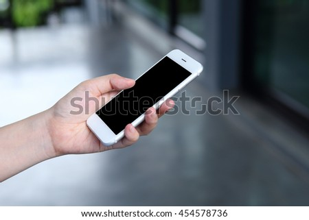 Hand holding mockup smartphone with office background - stock photo