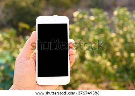 Hand holding mockup smartphone with tree background - stock photo