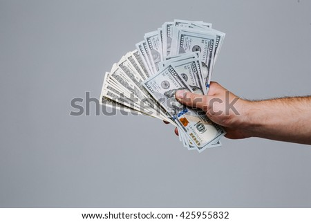 Hand holding money fan. One hundred dollar bills on a gray background. Banknote, close-up. The offer of a bribe. - stock photo