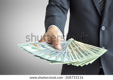 Hand holding money - United States dollar (USD) bills - stock photo