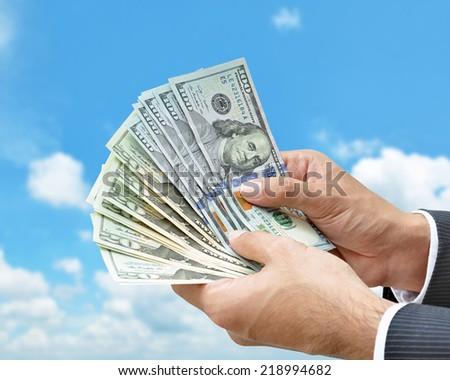 Hand holding money United States dollar (USD) bills on blue sky background - stock photo