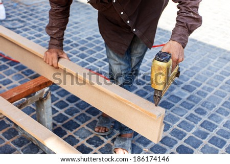 Hand holding nail gun to fix the wood - stock photo