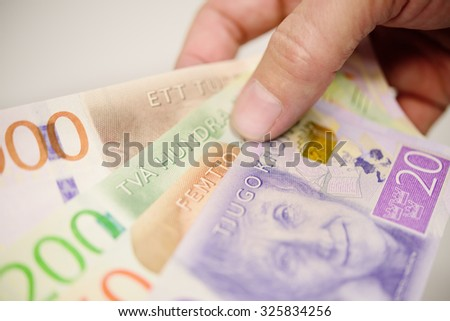 Hand holding new swedish bank notes fanned out. NOTE: the new 2015 model.