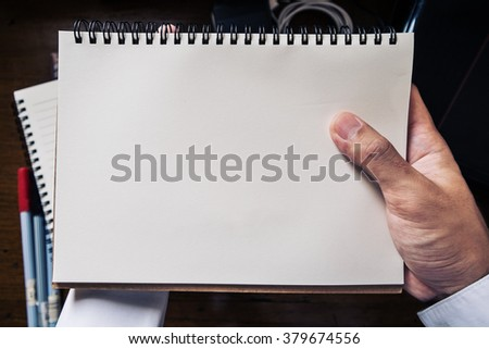 hand holding notebook - stock photo