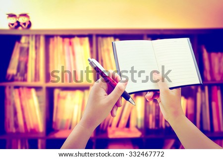 hand holding notebook and pen on blur book shelf background ,vintage tone - stock photo