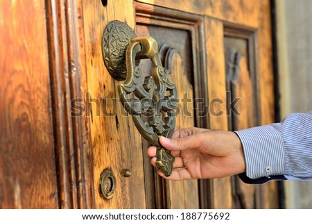 hand holding old door knocker  - stock photo
