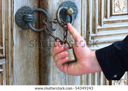 Hand holding old iron security lock of ornamental wooden door - stock photo