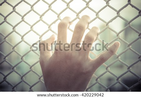 hand holding on chain fence - stock photo