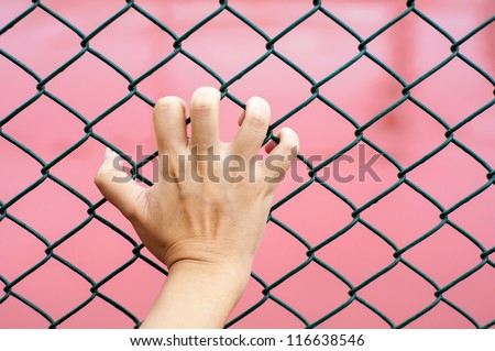hand holding on chain link fence, red background - stock photo