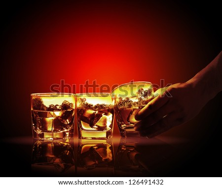 Hand holding one of three glasses of whiskey with nature illustration in