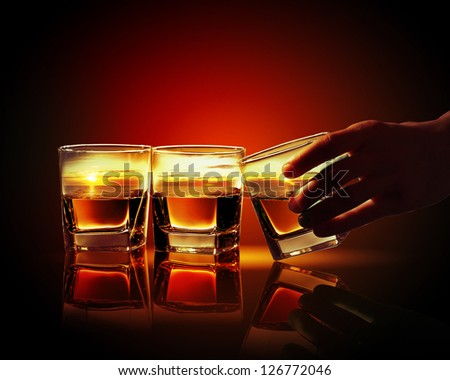 Hand holding one of three glasses of whiskey with sea illustration in - stock photo