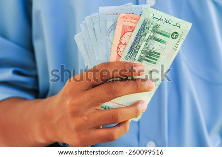 Hand holding or counting Malaysian Ringgit banknotes, selective focus shallow depth of field - stock photo