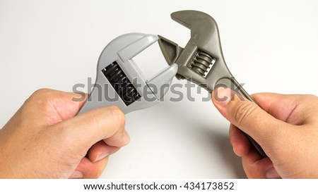 Hand holding or gripping spanner wrench tool. Isolated on white background. Slightly de-focused and close-up shot. Copy space.