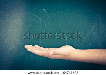 hand holding or showing your product in front of blackboard - stock photo