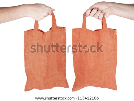 Hand holding orange fabric reusable shopping bag isolated on white - stock photo