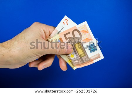 hand holding out a bill, on a blue background - stock photo
