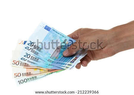 Hand holding out a fan of euros of different amounts - stock photo