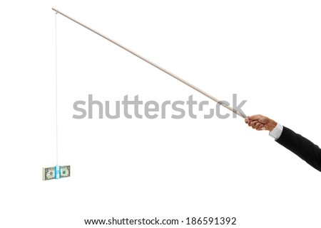 Hand holding out a stack of money tied to the end of a stick for bribery - stock photo