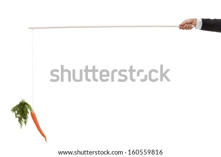 Hand holding out a stick with a string and a carrot attached - stock photo