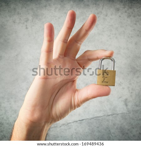 Hand holding padlock with British Pound currency symbol. Security and insurance concept. - stock photo