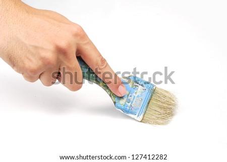Hand holding painting brush on white canvas - stock photo