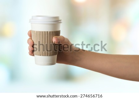 Hand holding paper cup of coffee on bright background - stock photo