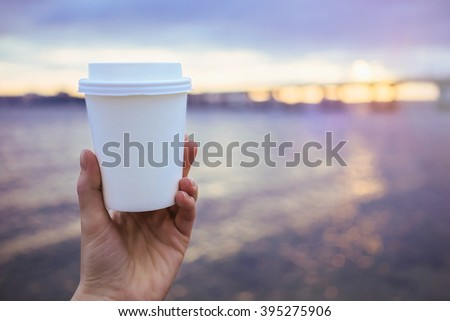 Hand holding paper cup of coffee on natural morning background. Film effect. - stock photo