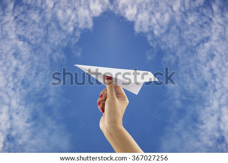 Hand holding paper plane on sky background - stock photo