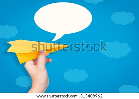 hand holding paper plane with speech bubble on blue background  - stock photo