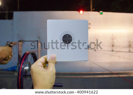 hand holding paper target practice in Practice shooting training field - stock photo