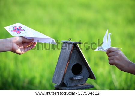 hand holding paper toy with bird house. - stock photo