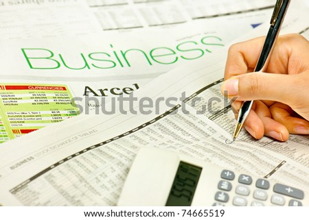 Hand holding pen on newspaper. - stock photo