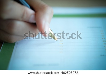 Hand holding pen over application form , selective focus , macro with blur ,vignette and soft focus , business concept ,business idea , signing finance - stock photo