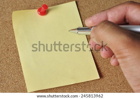 Hand Holding Pen to Write On Yellow Paper Note at Board Background, Selective Focus - stock photo