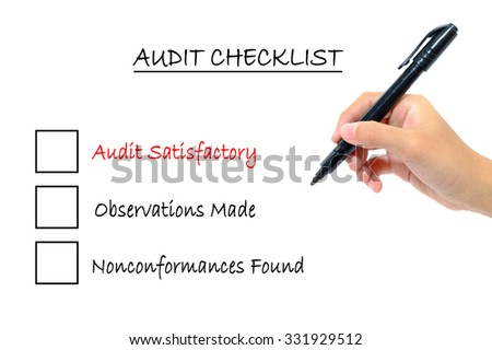 Hand holding pen writing words audit checklist concept.