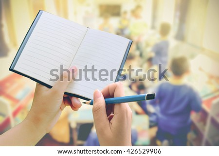 hand holding pencil and notebook with blur student in library background - stock photo