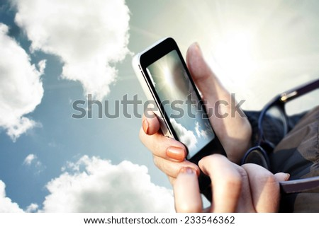 Hand holding phone. Sky photo. - stock photo