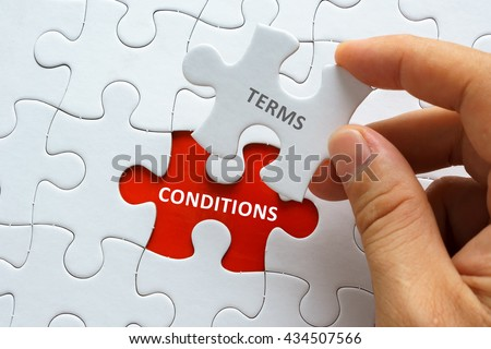 Hand holding piece of jigsaw puzzle with word TERMS CONDITIONS. - stock photo