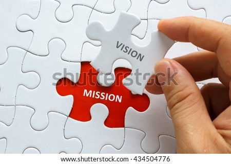 Hand holding piece of jigsaw puzzle with word VISION MISSION. - stock photo
