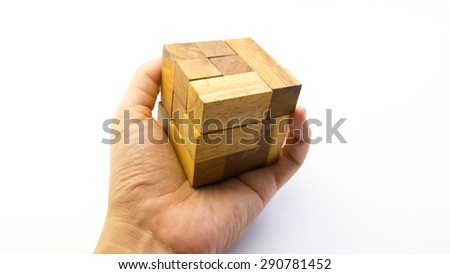 Hand holding piece of wooden block cube puzzle. Isolated on white background. Concept of complex and smart logical thinking. Slightly defocused and close up shot. Copy space. - stock photo
