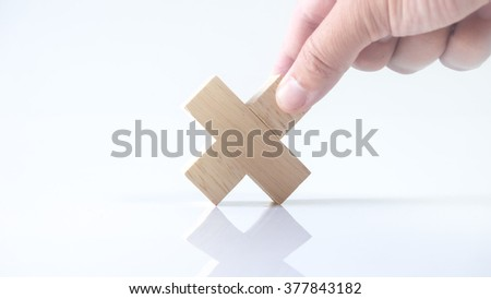 Hand holding piece of wooden block puzzle. Isolated on empty background. Concept of complex and smart logical thinking. Slightly defocused and close up shot. Copy space.