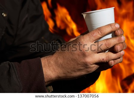 Hand Holding Plastic Cup With Fire In Background. - stock photo
