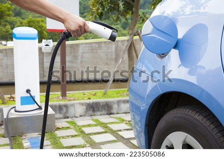 hand holding plug for Charging of an electric car - stock photo
